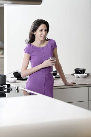 Attractive young woman in a dinner dress holding a glass of wine in her kitchen. photo