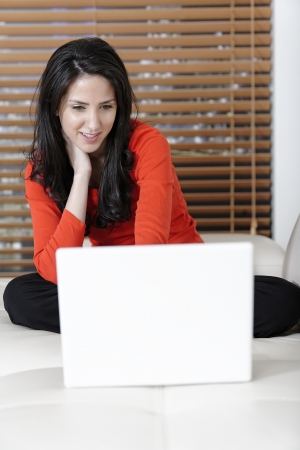 Attractive woman using her laptop in her living room.