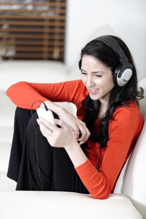 Attractive woman sat on a white sofa listening to music photo