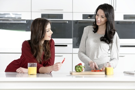 Two attractive young women preparing food in a white kitchen while talking.