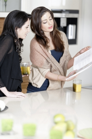 Two attractive young women reading from a cookery book in a kitchen Stock Photo