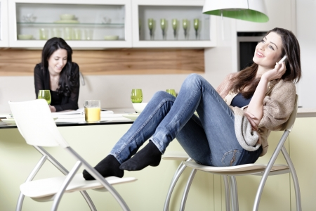 Two friends in a kitchen relaxing on the phone and reading