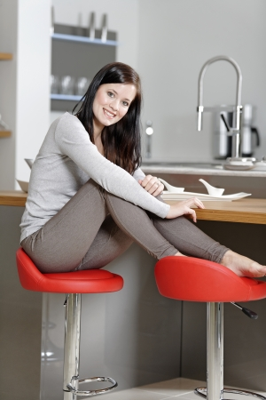 Attractive young woman taking a break in her kitchen with her feet up. photo