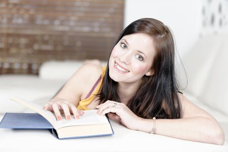 Attractive young woman lying on her sofa with a book. photo