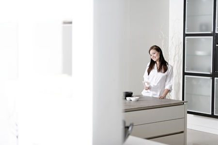 Beautiful young woman relaxing in her elegant white kitchen Stock Photo - 18919705
