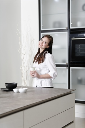 Beautiful young woman relaxing in her elegant white kitchen Stock Photo - 18919725