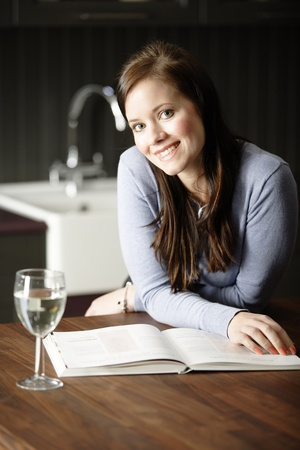 Attractive young woman reading a recipe from a cookery book in her kitchen with a glass of wine. photo