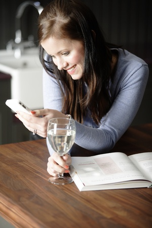 Attractive young woman enjoying a glass of wine in her kitchen while texting on the phone. photo