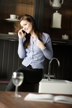 Attractive young woman enjoying a glass of wine in her kitchen while chatting on the phone. photo