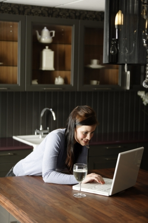 Attractive young woman using her laptop in the kitchen photo