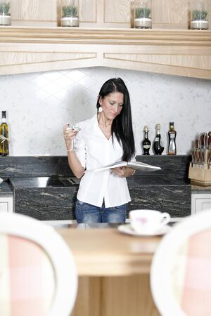 Attractive young woman reading a recipe from a cookery book in her kitchen. photo