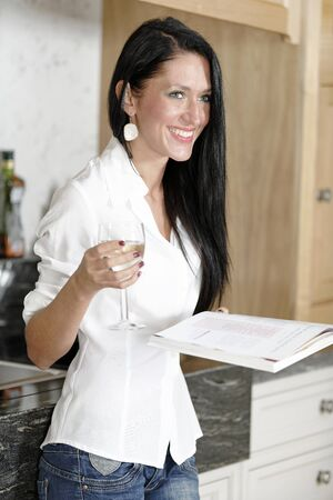 Attractive young woman reading a recipe from a cookery book in her kitchen. Stock Photo - 18938346