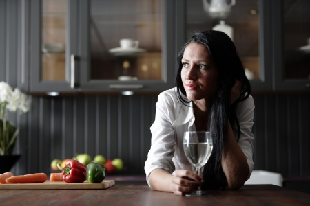 farmhouses: Attractive young woman enjoying a glass of wine in her kitchen.