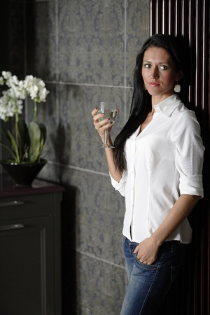 Attractive young woman enjoying a glass of wine in her kitchen. photo