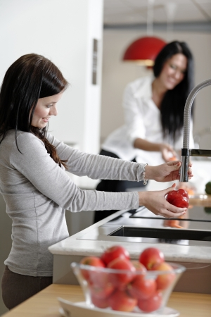 Two attractive friends preparing food in their kitchen at home.