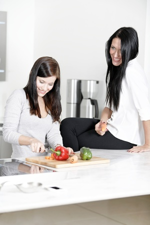 Two attractive friends preparing food in their kitchen at home. photo