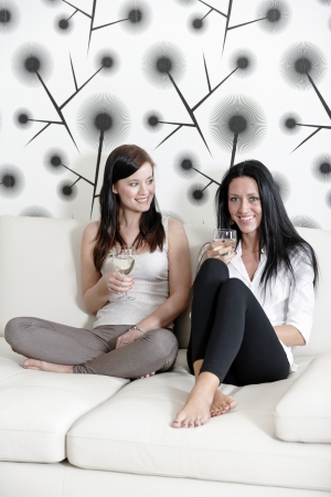 Two attractive young friends catching up at home on the sofa with a glass of wine. photo
