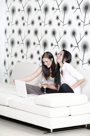 Two attractive young friends catching up at home on the sofa with a glass of wine using a laptop computer. Stock Photo