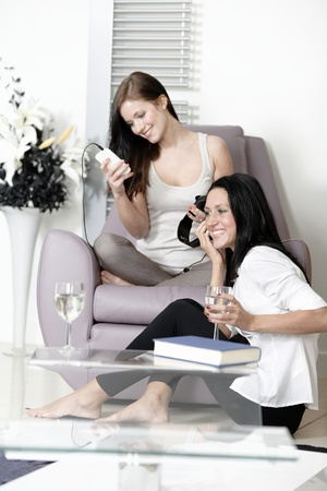 Two beautiful young woman listening to music on headphones at home on a chair.