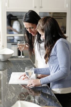 Two attractive friends looking at recipes in a cookery book in their kitchen.
