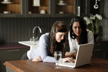 Two attractive friends looking at recipes on a laptop in their kitchen.