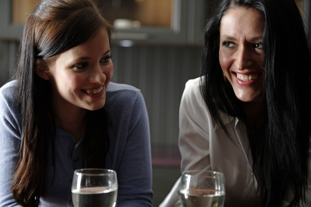 Two attractive young friends laughing and drinking wine in their kitchen. Stock Photo - 18940061