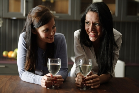 Two attractive young friends laughing and drinking wine in their kitchen. Stock Photo - 18940060