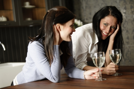Two attractive young friends laughing and drinking wine in their kitchen. photo