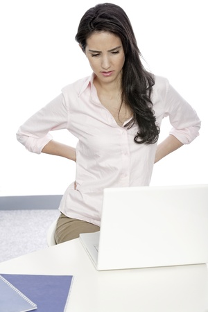 Beautiful young woman with back pain at her office desk Stock Photo - 19070782