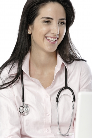 Beautiful young doctor sat smiling at her work desk using her computer. Stock Photo - 19070988
