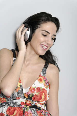 Attractive young woman using headphones to listen to music Stock Photo - 19070999