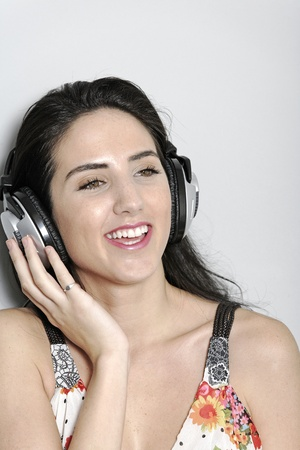 Attractive young woman using headphones to listen to music Stock Photo - 19070990