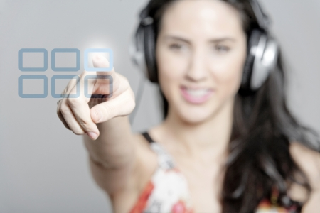 Woman selecting a song to listen to by pressing a concept button Stock Photo