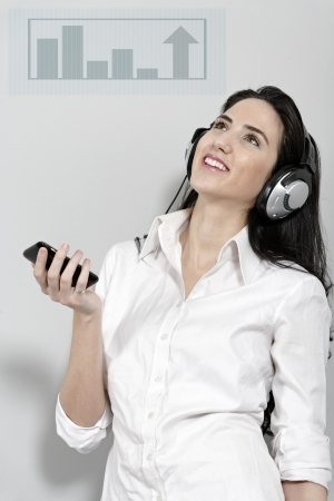Attractive young woman holding out her mobile phone which is displaying a volume graph Stock Photo - 19070874