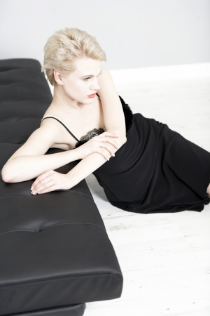 Attractive young woman in a black night dress relaxing on a sofa at home. photo