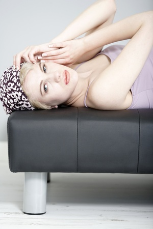 Beautiful young woman relaxing on her sofa at home in pyjamas. photo