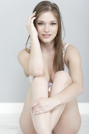 Attractive young woman in underwear siting on the floor.