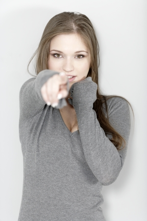 Attractive young woman pointing with her finger.