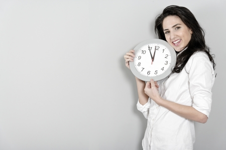 Beautiful young woman holding up a clock face photo