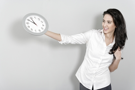Concept of young woman holding a clock at arms length photo