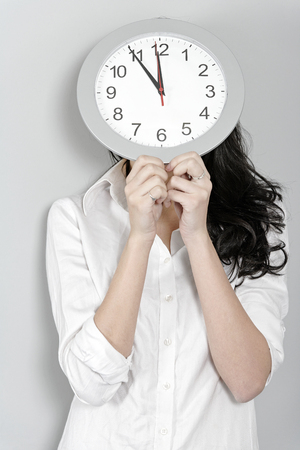 Beautiful young woman holding up a clock to her face. photo