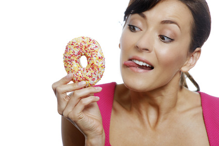 guilty pleasures: Young woman holding a doughnut looking guilty