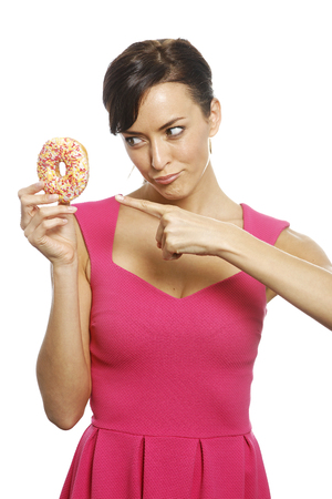 guilty pleasure: Young woman holding a doughnut looking guilty