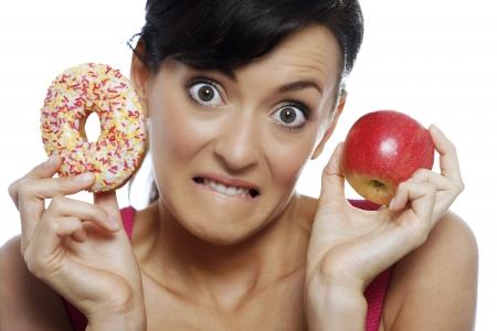 guilty pleasures: Young woman deciding between an apple or doughnut.