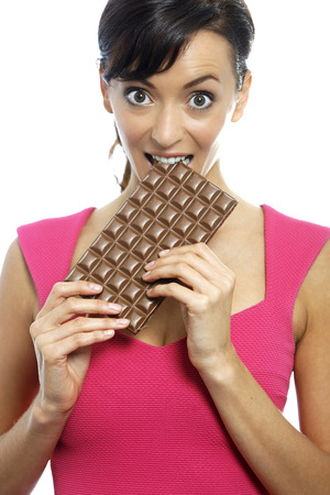 guilty pleasures: Young woman eating a huge chocolate bar