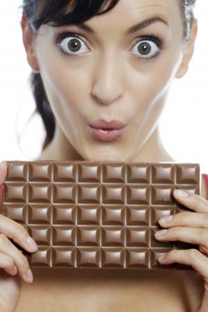guilty pleasure: Joven mujer comiendo una enorme barra de chocolate