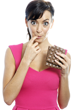 guilty pleasure: Young woman eating a huge chocolate bar