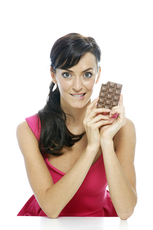 guilty pleasure: Woman eating a huge chocolate bar Stock Photo