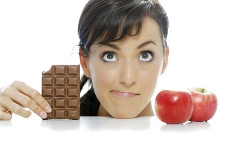 guilty pleasure: Mujer joven dividido entre una barra de chocolate y manzana fresca