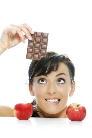 Mujer joven dividido entre una barra de chocolate y manzana fresca Foto de archivo - 23462806